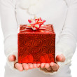 Women's hands hold out a box with a gift — Stok fotoğraf