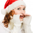 Young beautiful woman in a Santa hat whispers — Stock Photo #13683650