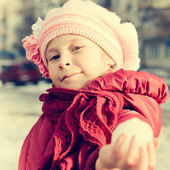 Young girl holds out his hand in a snowball — Stock Photo