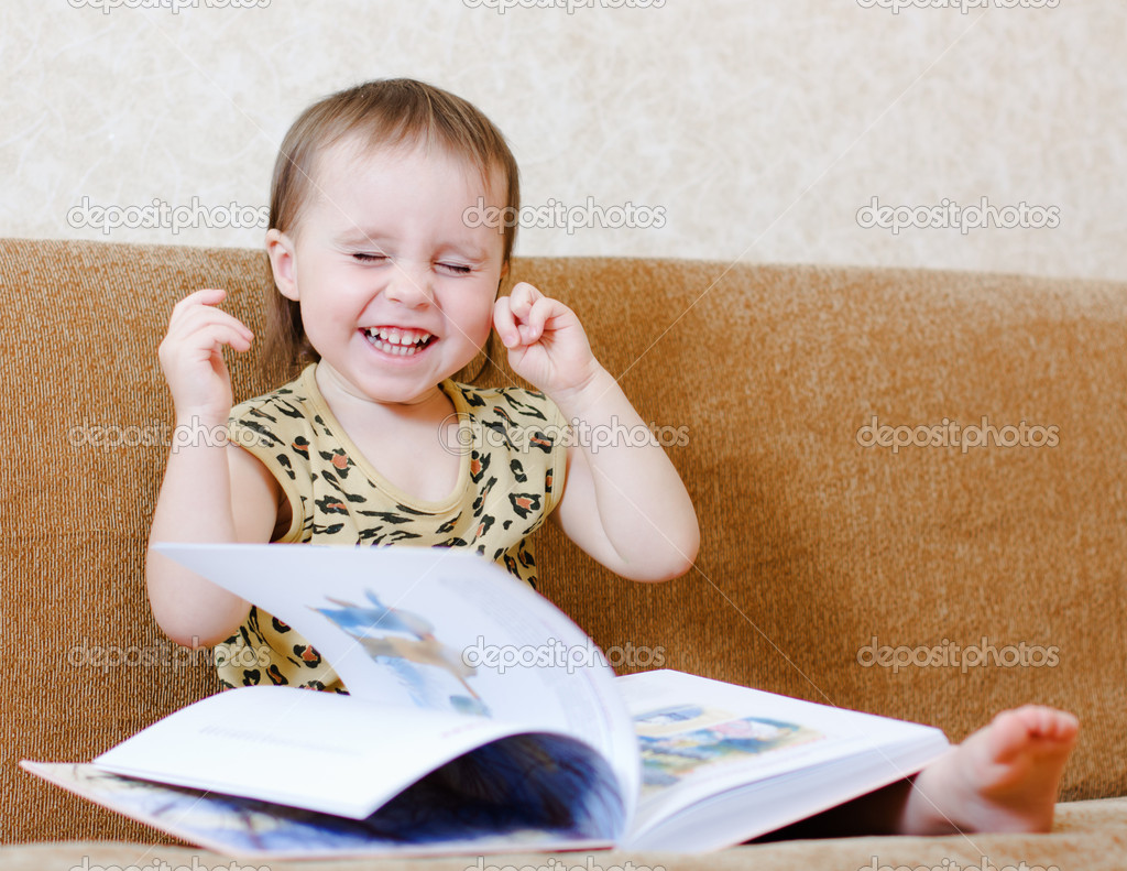 Beautiful cute baby reading a book while sitting on the couch. — Stock Photo #16044267