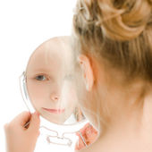 Pretty beautiful girl looks in the mirror. — Stock Photo