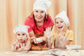 Mother with two daughters baking bread. — Stock Photo
