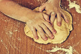 Diligent children hands make a dough. — Stock Photo