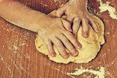 Diligent children hands make a dough. — Stock Photo