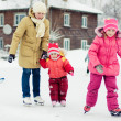 Mom and her daughters skating - Stock Photo