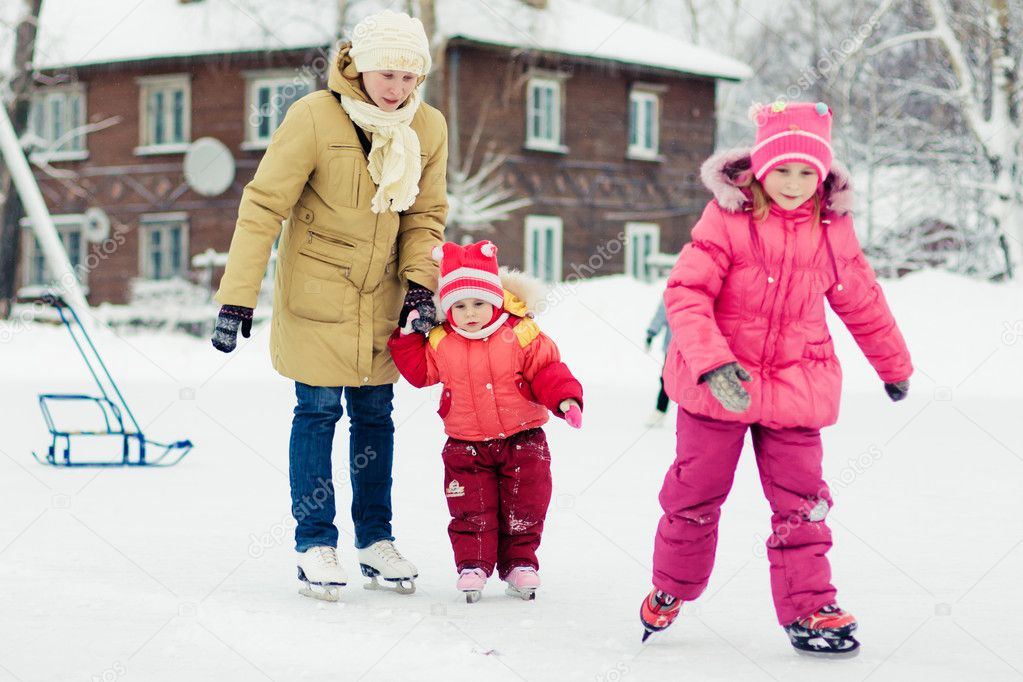 Mother with her daughters skates on ice skating in the winter.  Stock Photo #21280267