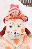 Happy baby sitting on a snowman — Stock Photo