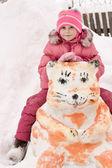 Szczęśliwe dziecko siedzi na bałwanka — Zdjęcie stockowe