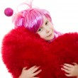 A girl with pink hair and a pink dress cuddle pillow in the form of the hea — Stock Photo #8789719