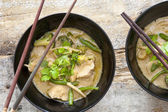 Bowls of Thai green curry with chopsticks — Stock Photo