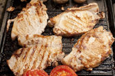 Grilled pork chops and tomatoes on a griddle — Stock Photo