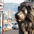 Cars on road behind lion statue - Stock Photo