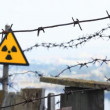 Radioactivity Sign and barbed wire. - Stock Photo