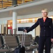 Businesswoman in black suit with luggage — Lizenzfreies Foto
