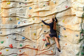 Young business woman on rock wall — Stock Photo