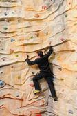Man on rock wall in sport center — Stock Photo
