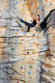 Woman on rock wall in sport center — Stock Photo