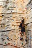 Business woman on rock wall — Stock Photo