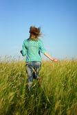 Mujer huir a través de la hierba alta — Foto de Stock