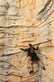 Business woman on rock wall — Stock Photo