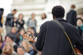 Male musician playing in the street near Sacre Coeur for money — Stock Photo