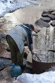 Homme recueille l'eau dans un bidon — Photo