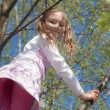 Cheerful little girl on spring tree — Stock Photo