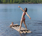 Girl on a wooden raft — Stock Photo