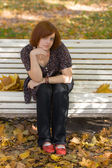 Girl on autumn park bench — Stock Photo