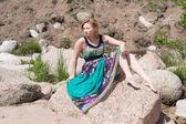 在一块岩石上穿裙子的女孩 — 图库照片