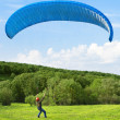 Stock Photo: Paraglider. Mwith parachute struggling with wind.