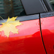 Stock Photo: Autumn maple leaf as label stuck to car