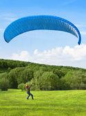 Parapente. hombre con paracaídas luchando con el viento. — Foto de Stock