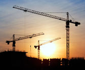 Silhouettes of construction cranes against the evening sky — Stock Photo