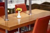 Jarrón con flores sobre una mesa en un café en el centro comercial — Foto de Stock
