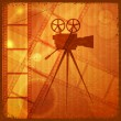 Vintage orange background with the silhouette of movie camera — Vector de stock