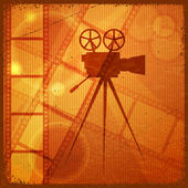 Vintage orange background with the silhouette of movie camera — Stock Vector