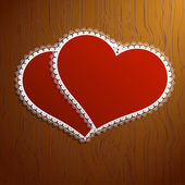 Two lacy red hearts on a wooden background — Stock Photo