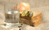 Glass of vodka, bread and pickled cucumber — Stock Photo