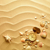 Beach sand background and antique compass — Stock Photo
