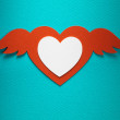 Valentine heart with angel wings made of paper on blue paper background — Stock Photo