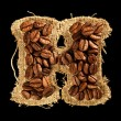 Alphabet from coffee beans on fabric texture isolated on black — Lizenzfreies Foto