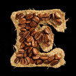 Alphabet from coffee beans on fabric texture isolated on black — ストック写真
