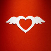 Valentine heart with angel wings made of paper on red paper background — Stock Photo