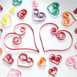Hearts made of paper stripes on white paper background - Foto Stock