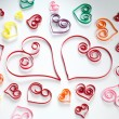 Hearts made of paper stripes on white paper background - Stockfoto