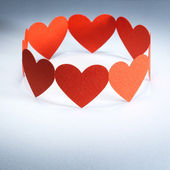 Group of red valentine hearts connected in chain, paper craft — Stock Photo
