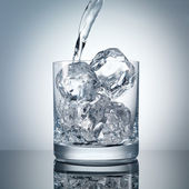 Pouring water into a glass with perfect ice — Stock Photo