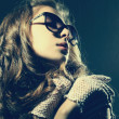 Fashion portrait of a beautiful young woman wearing sunglasses - Stock Photo