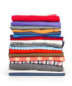 Stacks of colorfull clothes on white background — Stockfoto
